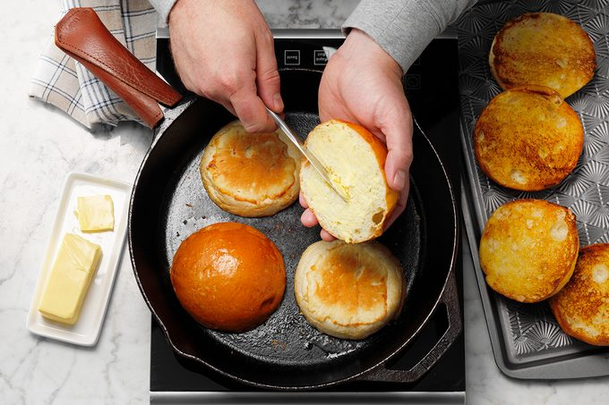 Easy Grilled Hamburgers; How to; marble surface; overhead camera angle; induction; cast iron skillet; cast iron pan; TOH Baking Pan 13x9; Metal bakeware; burger; hamburger; burgers; hamburgers; buns; rolls; burger buns; butter; buttered; grilled; toasted; hands; prep; in process; step #4 placing buttered bun on cast iron skillet; striped cloth