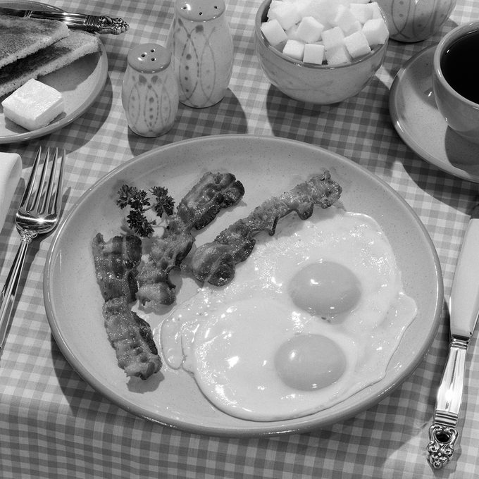 1950s BREAKFAST PLATE OF BACON AND FRIED EGGS AND COFFEE SUGAR BOWL TOAST SALT AND PEPPER SHAKERS ON CHECKERED TABLECLOTH (Photo by L. Fritz/ClassicStock/Getty Images)