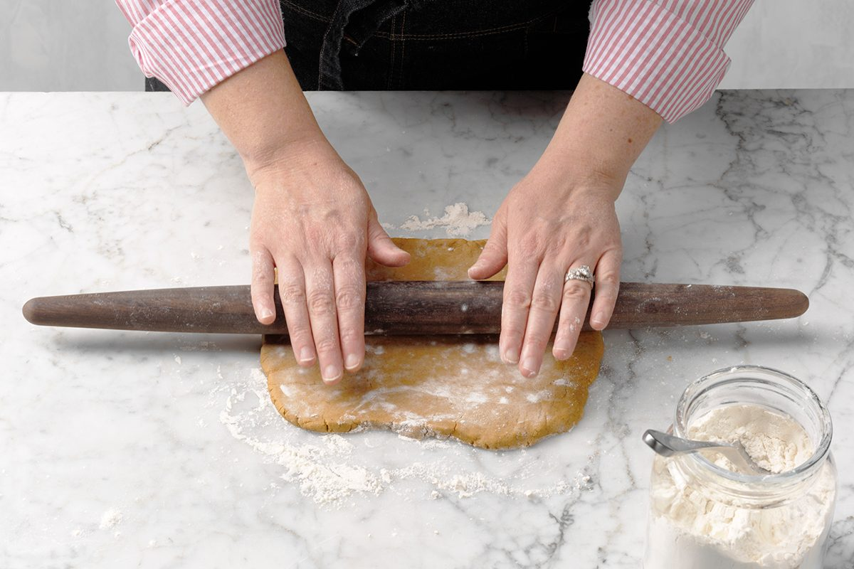 Rolling out cookie dough with a French rolling pin