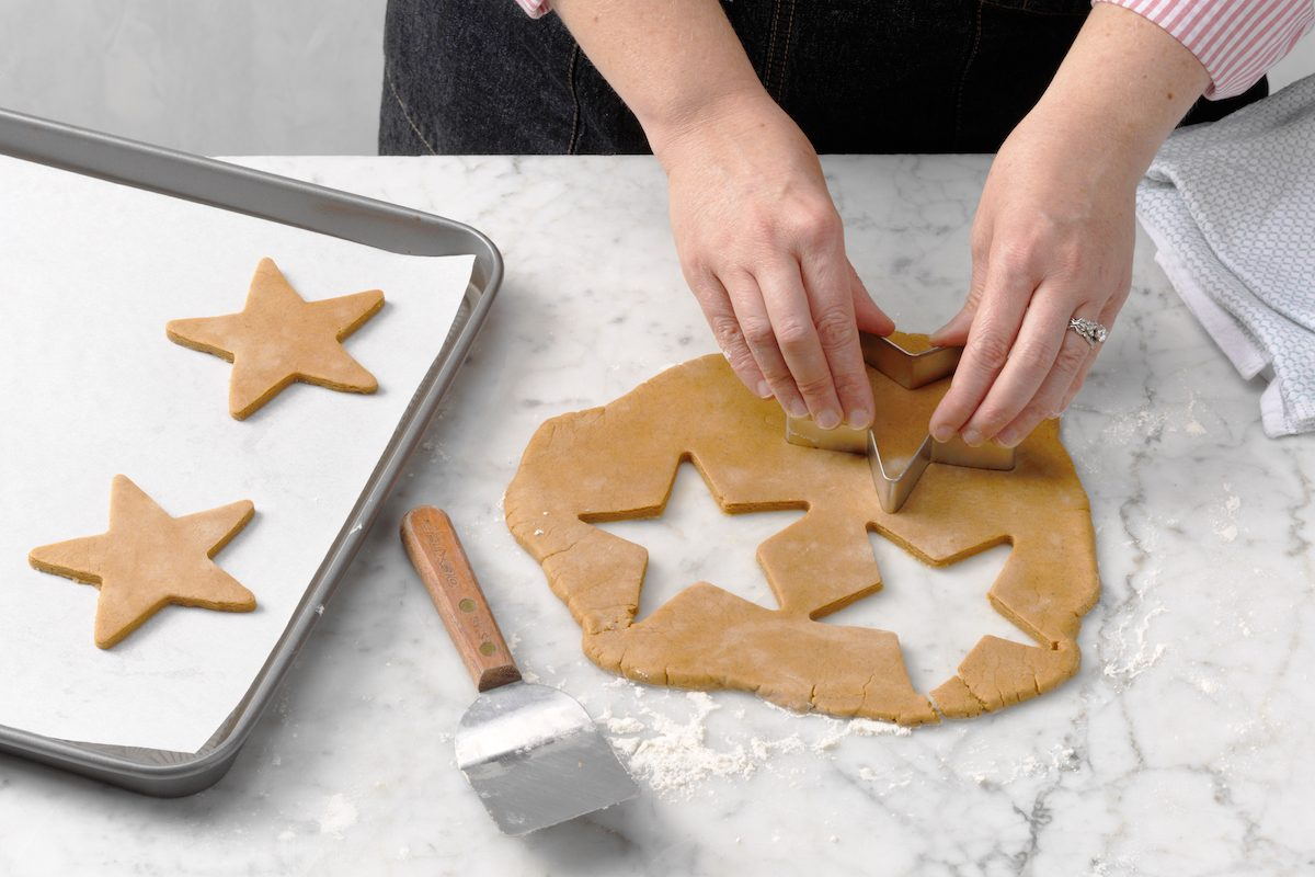 Hands using a star-shaped cookie cutter to cut cookie dough.