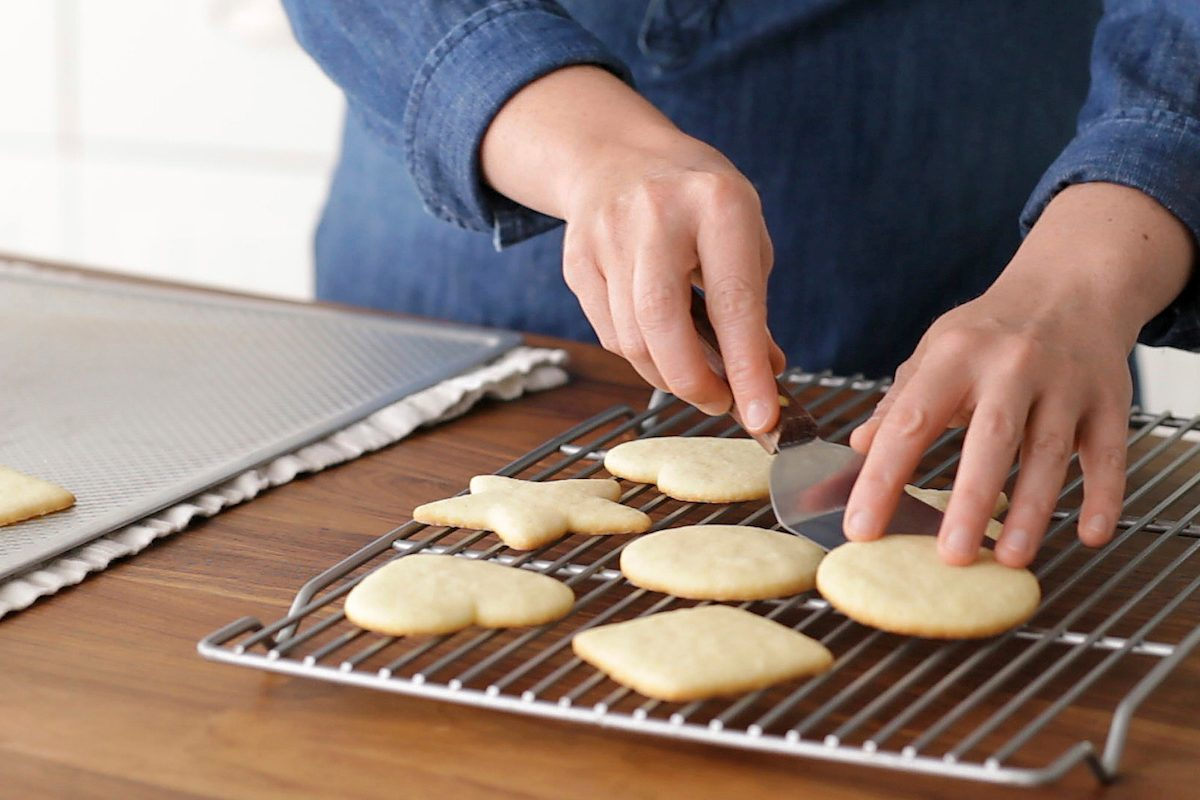 Hands transferring cutout cookies to a wire cooling rack.