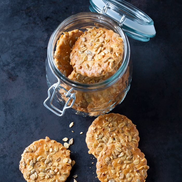 A glass storage container of granola cookies.
