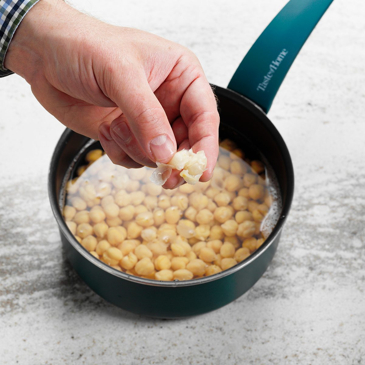 A person removing the skins from a pot of chickpeas in order to make homemade hummus.