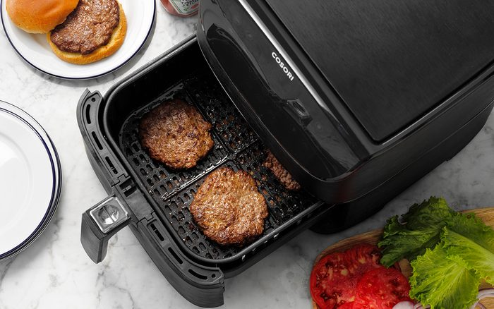 Easy Grilled Hamburgers; How to; marble surface; overhead camera angle; step #5; burger patties in air fryer basket not touching; veggie tray; lettuce; onions; tomato; tomato slices; hamburger; burger; white plates; ketchup; ketchup bottle; prep; in process
