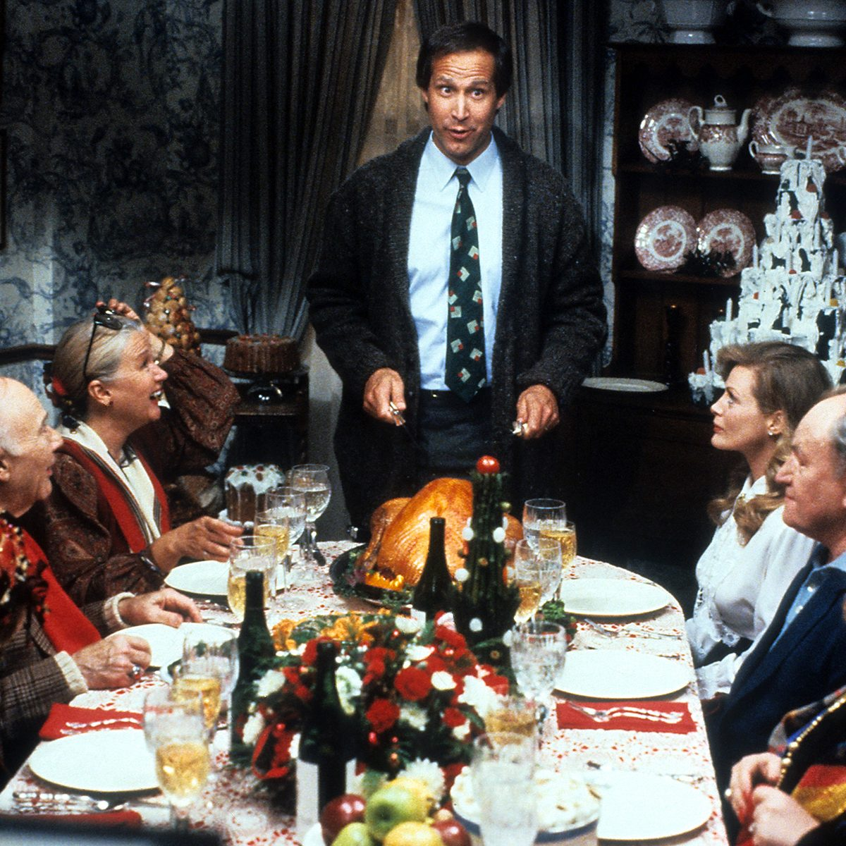 Chevy Chase stands at the head of the table in a scene from the film 'Christmas Vacation', 1989. (Photo by Warner Brothers/Getty Images)