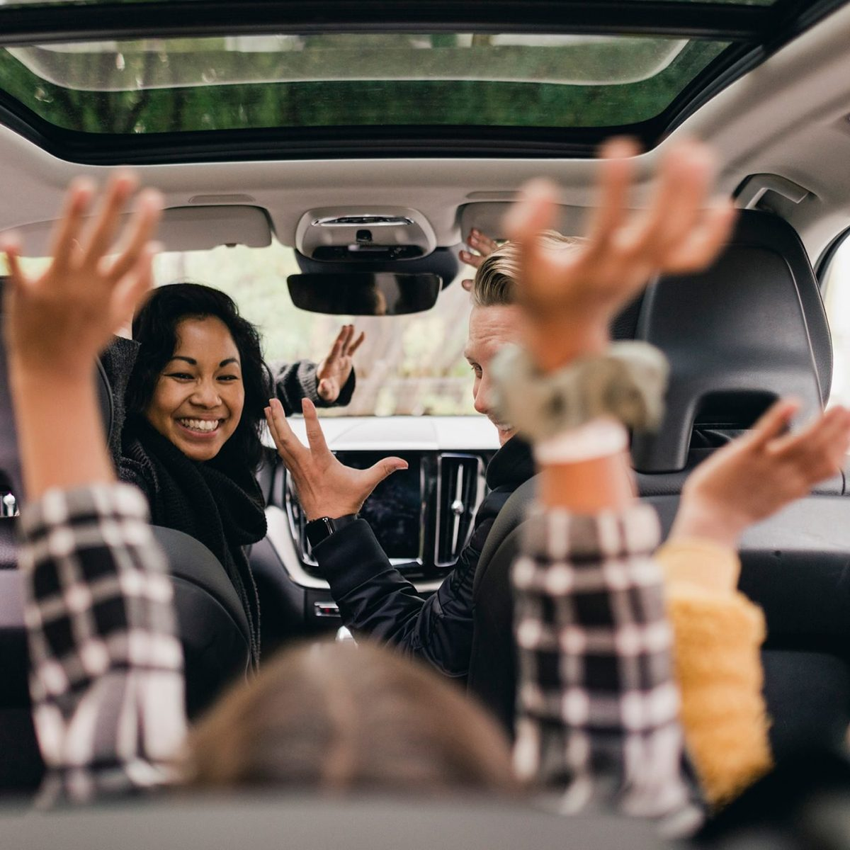 Cheerful family raising hands while enjoying road trip in electric car