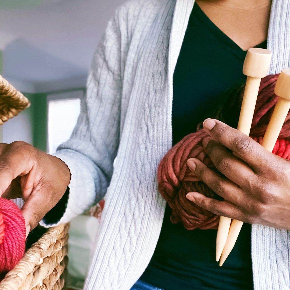 Close-up of unrecognizable woman holding a skein of super bulky hand dyed yarn and pair of giant knitting needles while searching her stash