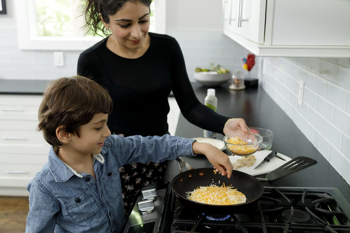 A mother looks on as her son makes a quesadilla. He is adding shredded cheese to a tortilla to the frying pan. He is five years old and is wearing a long sleeved blue shirt, his mother is in a black long sleeved top. Her hair is tied back. They are in a home kitchen with white tiles and white cabinets. They are cooking on a gas range top stove. They are both looking at the food being prepared.