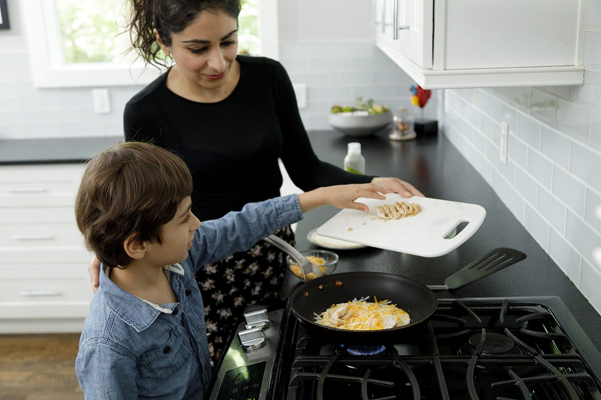 A mother looks on as her son makes a quesadilla. He is adding chicken to the shredded cheese and tortilla in the frying pan. He is five years old and is wearing a long sleeved blue shirt, his mother is in a black long sleeved top. Her hair is tied back. They are in a home kitchen with white tiles and white cabinets. They are cooking on a gas range top stove. They are both looking at the food being prepared.