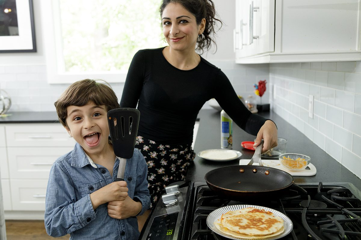 A mother teaches her son how to make a quesadilla. He is posing proudly next to the finished product on a plate beside him. He is five years old and is wearing a long sleeved blue shirt, his mother is in a black long sleeved top. Her hair is tied back. They are in a home kitchen with white tiles and white cabinets. They are cooking on a gas range top stove. They are both looking at the camera and smiling.