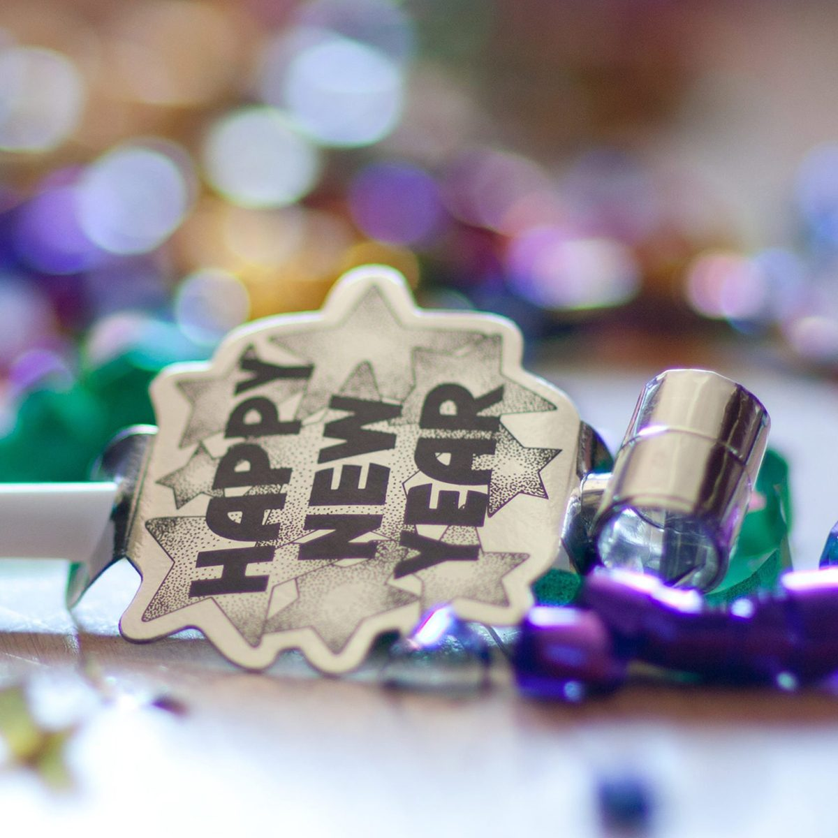 After the new year's eve party. A single party horn blower is found on the floor with fun, colorful confetti.