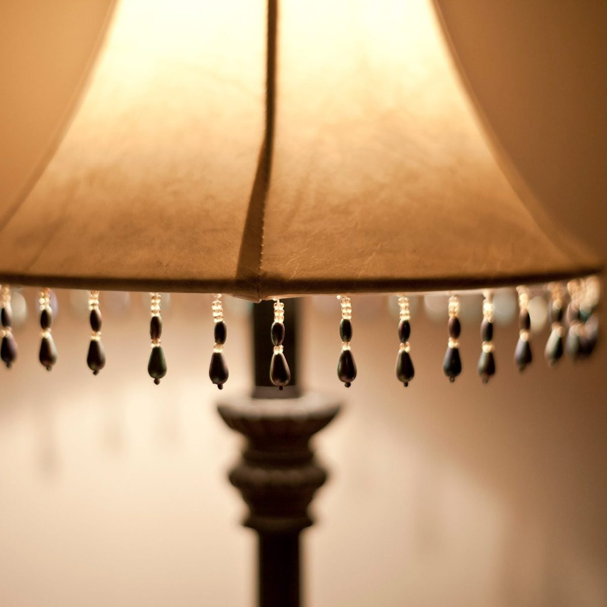 Close-up Of an illuminated lamp in a dark room, with bead detail on the lamp shade.