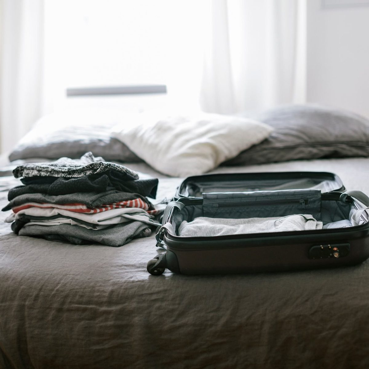 Open suitcase with clothing on Bed