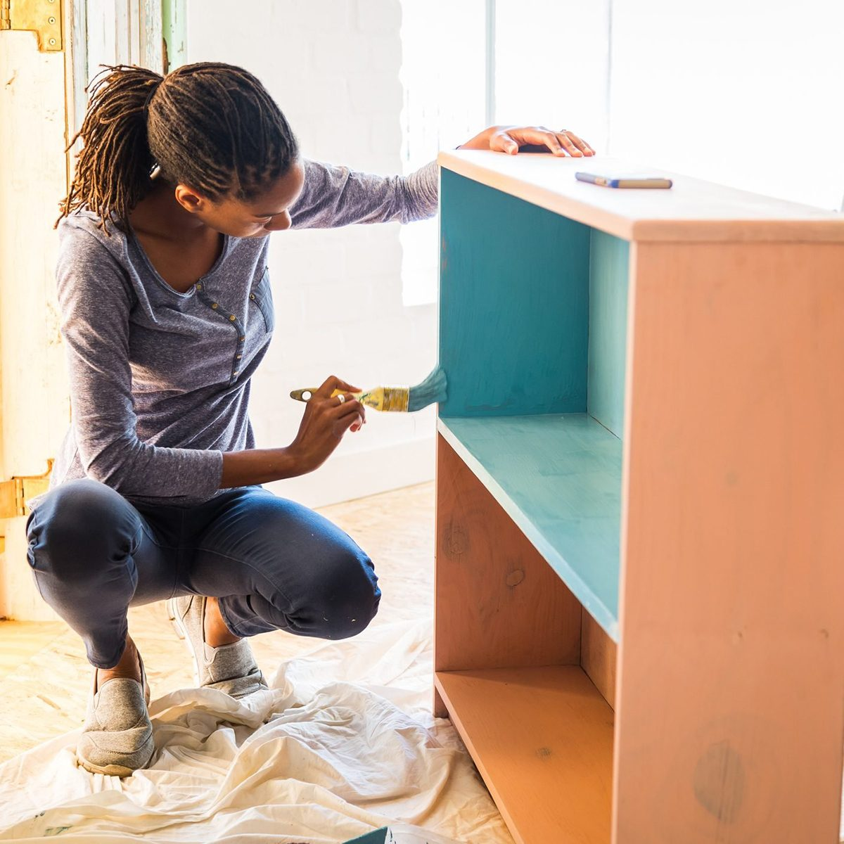 Young Afro-Caribean woman renovating her home