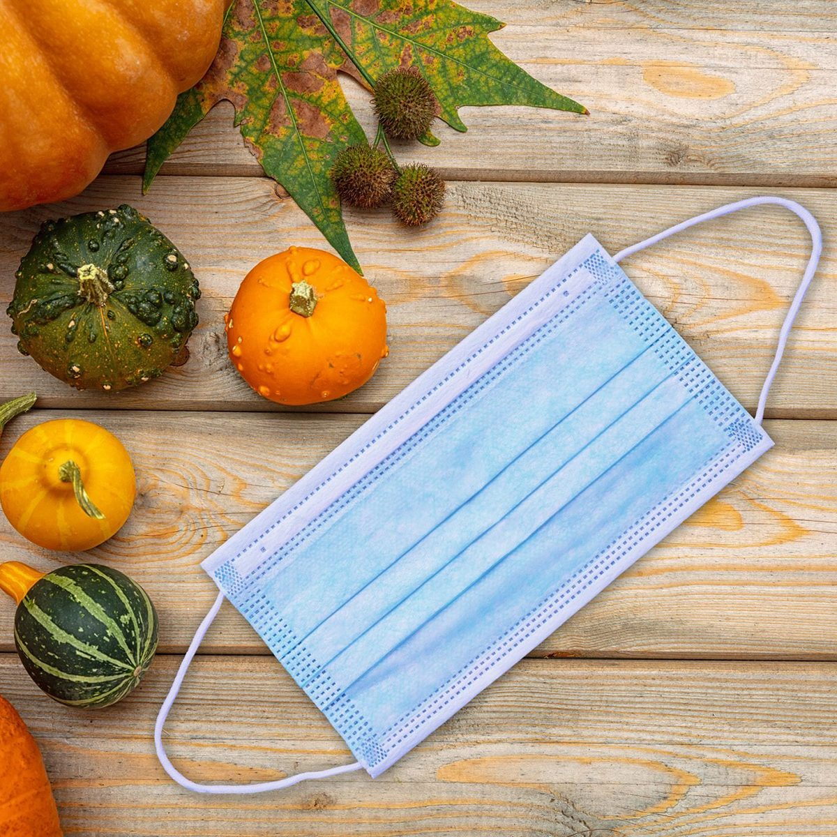 Thanksgiving 2020, coronavirus days, Protective face mask and colorful pumpkins on wooden background. COVID 19 spread prevention measure