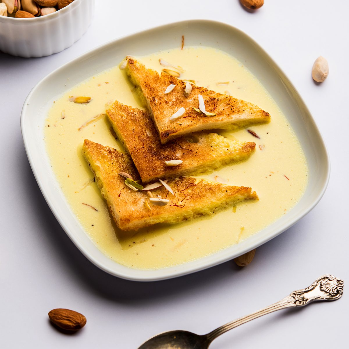shahi tukra/tukda or Double ka meetha is a bread pudding Indian sweet of fried bread slices soaked in rabid or sweet saffron milk garnished with dry fruits, selective focus