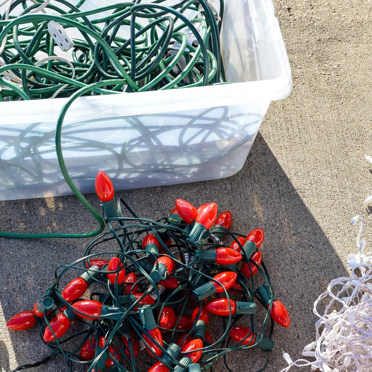 Outdoor holiday lights laid out on a driveway next to a plastic storage bin full of extension cords.