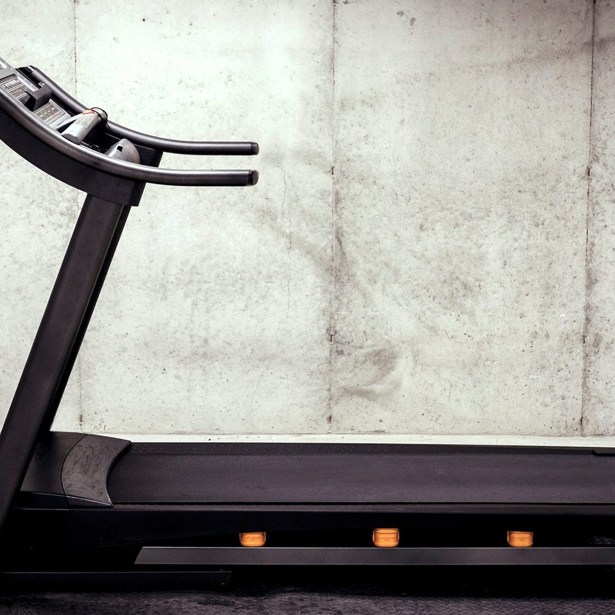 A treadmill sitting vacant just waiting for someone to run on it. The treadmill is sitting in a concrete basement.