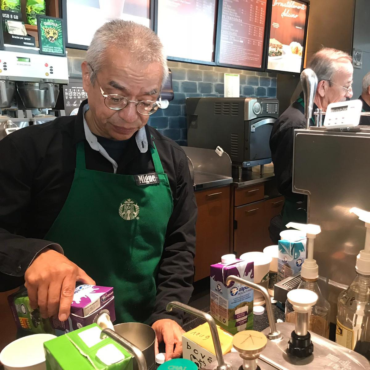 """30 October 2018, Mexico, Mexiko-Stadt: Miguel Angel Martinez Sarmiento works as a barista in a branch of the US coffee house """"Starbucks"""" and pours milk into a can. All the employees at the coffee shop, which opened in Del Valle Sur at the beginning of September, are over 60 years old. (to dpa """"US coffee house operates senior branch in Mexico City"""" from 01.11.2018) Photo: Antonia Märzhäuser/dpa (Photo by Antonia Märzhäuser/picture alliance via Getty Images)"""