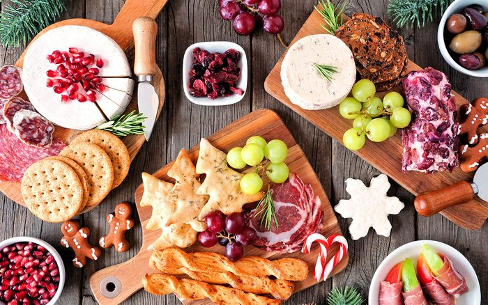 Christmas theme charcuterie table scene against a dark wood background. Assortment of cheese and meat appetizers. christmas cheese board