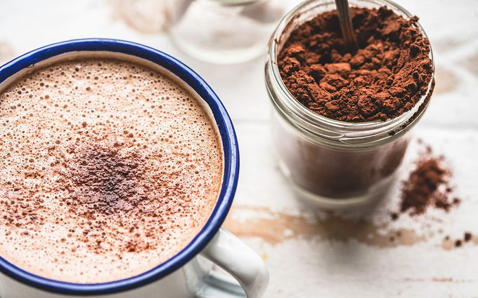 A warm cup of Hot Chocolate, on a rustic white-washed timber table top, with a jar of cacao on the side.