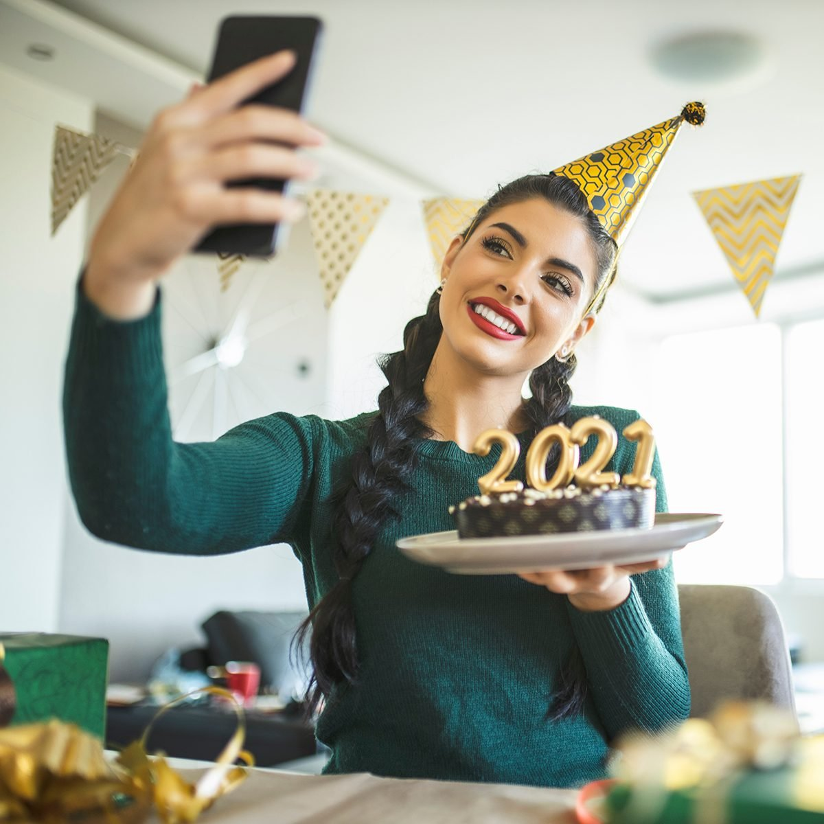 Beautiful young woman having video call while she preparing for new year, making a cake and wrapping gifts