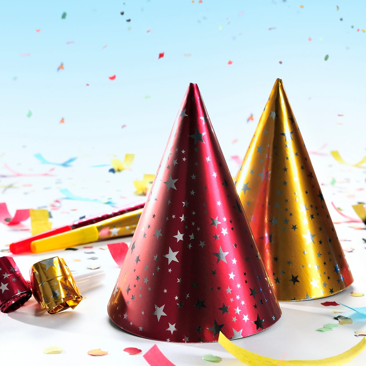 Party decorations: hats, whistles, horns, confetti on gradient blue background. Copy space, studio shot. This picture fits to New Year's, Parties, Birthdays topics.