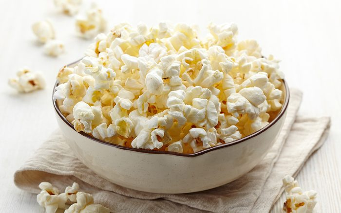 Bowl of fresh popcorn on white wooden background - how to make air popped popcorn