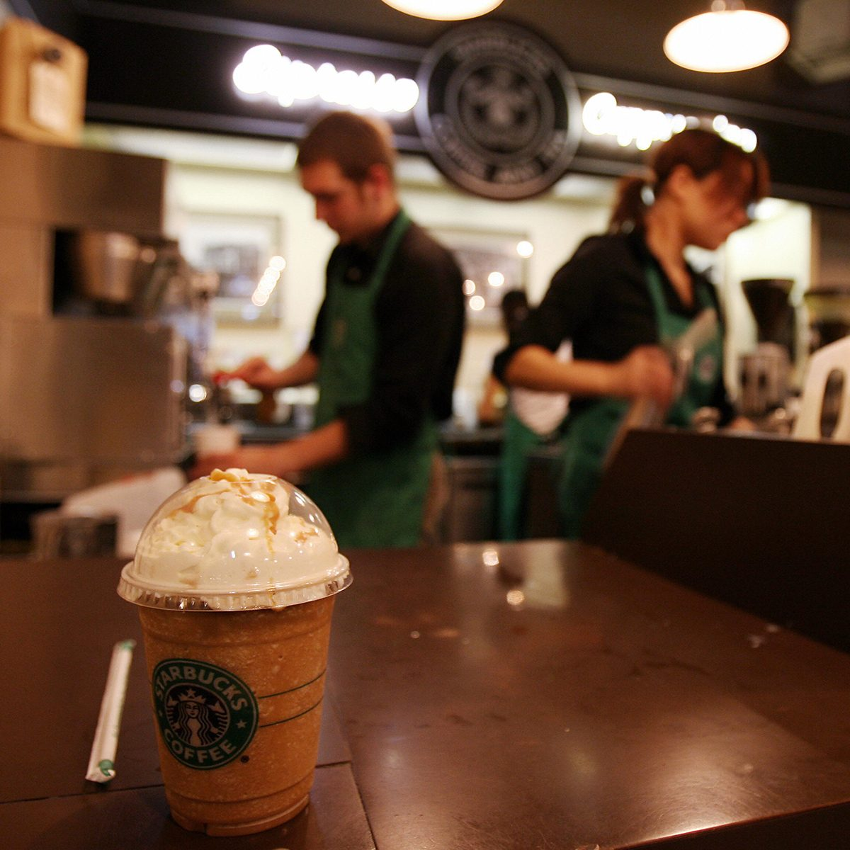 Seattle, UNITED STATES: Employees prepare beverages in the first Starbucks coffee shop in Seattle, 30 September 2006. Starbucks Corp. said it would raise most beverage prices at its US and Canadian coffee shops by five cents USD next month to help offset increased costs for fuel and labor. Starbucks opened its first location in Seattle's Pike Place Market in 1971. AFP PHOTO/GABRIEL BOUYS (Photo credit should read GABRIEL BOUYS/AFP via Getty Images)