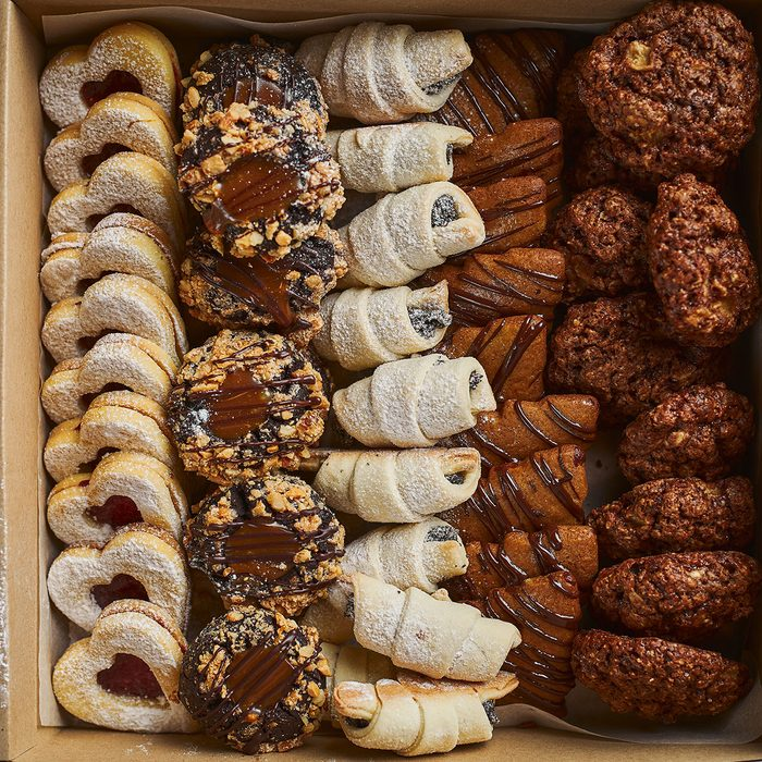 Top view of various mini Christmas pastry in the cardboard box on wooden table