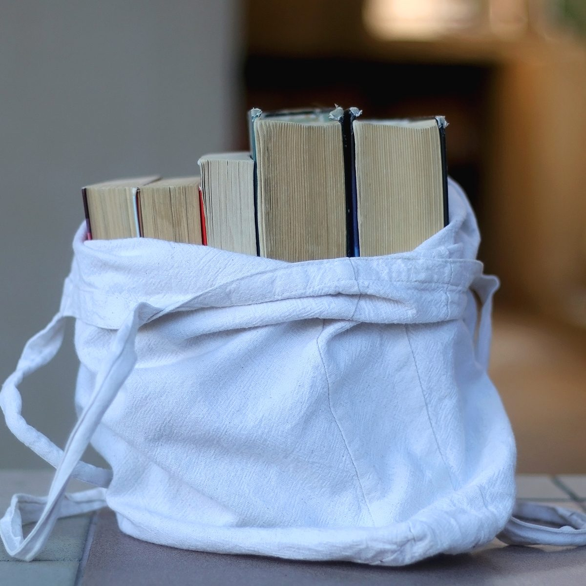 Canvas tote bag filled with old books. Selective focus.