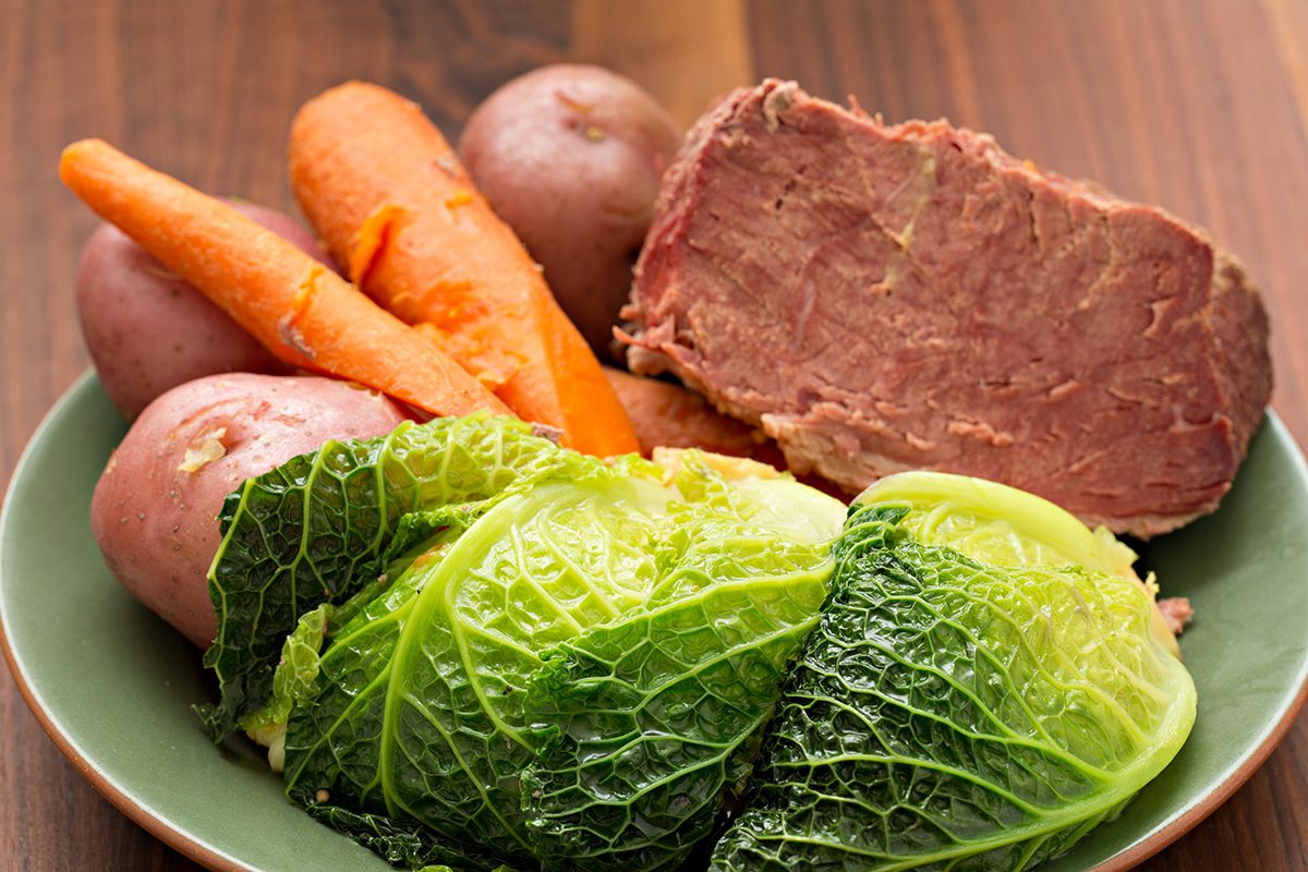 A high angle close up shot of some corned beef, cabbage, carrots and red potatoes on a green plate.