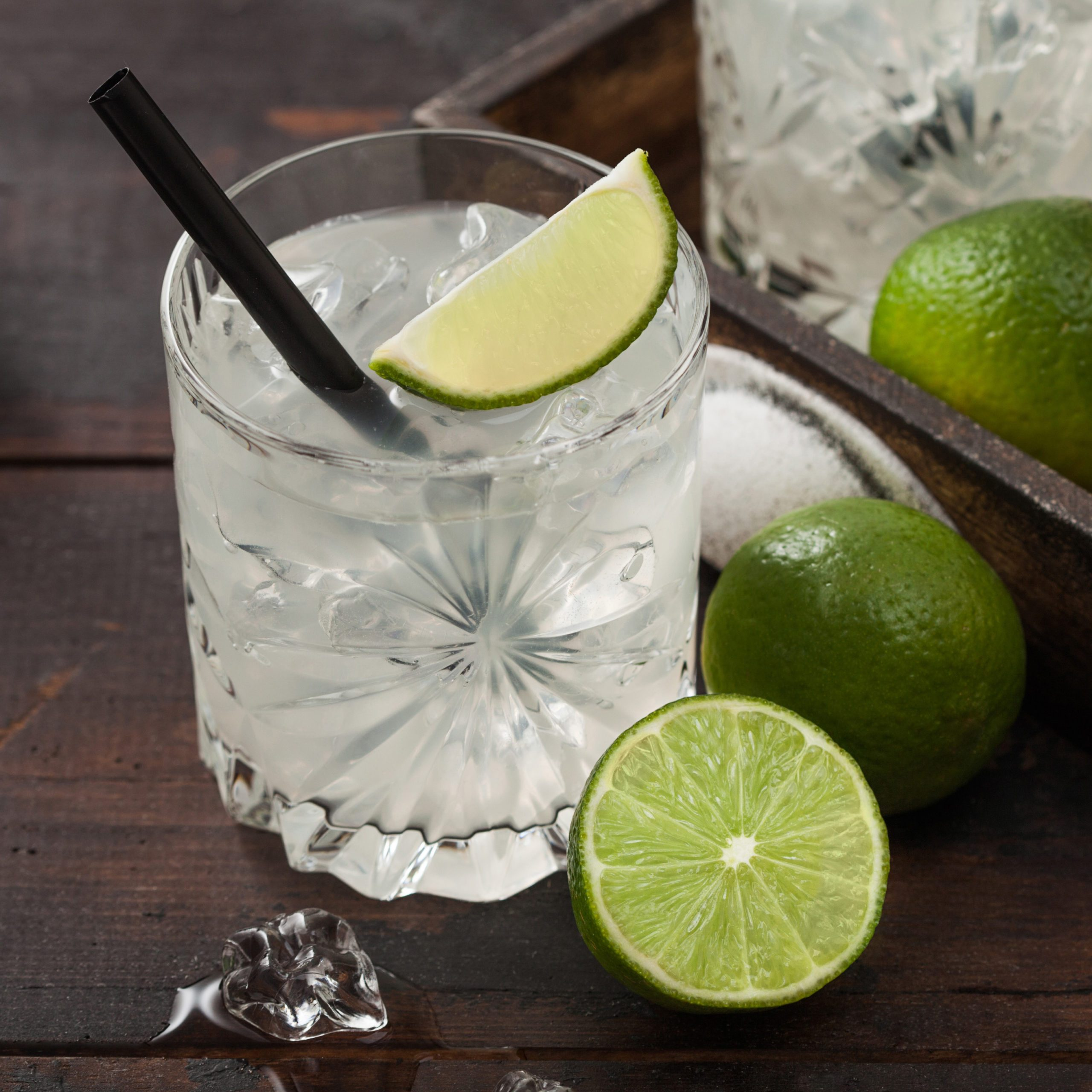 Gimlet Kamikaze Cocktail In Crystal Glasses With Lime Slice And Ice On Wooden Board With Fresh Limes And Jigger With Strainer.