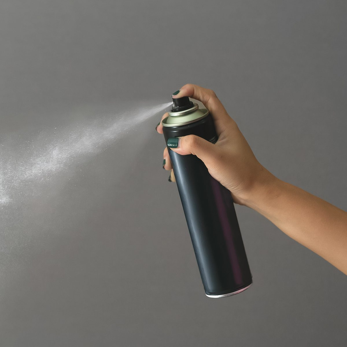 Cropped Hand Of Woman Spraying Against Gray Background