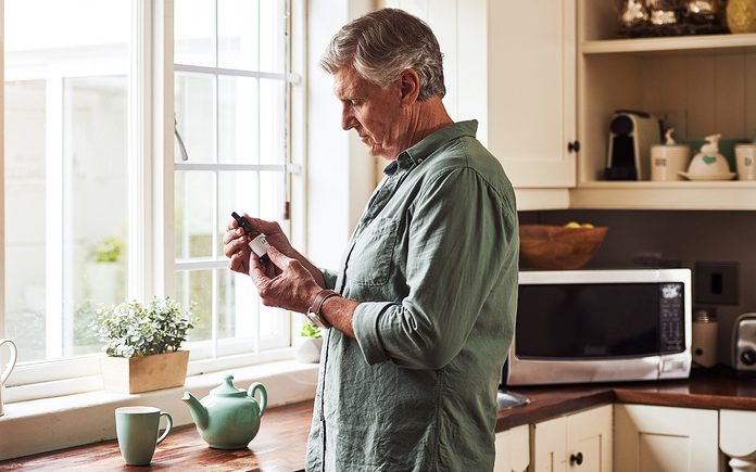 cooking with CBD oil Cropped shot of a relaxed senior man preparing a cup of tea with CBD oil inside of it at home during the day