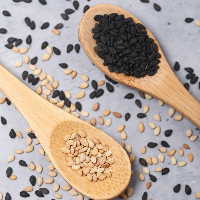 Sesame and black sesame in wooden spoons on cement background
