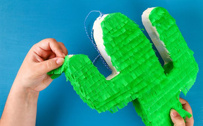 how to make a pinata Diy cinco de mayo Mexican Pinata Cactus made cardboard and crepe paper your own hands on a blue background. Gift idea, decor, game cinco de mayo. Step by step. Top view. Process kid children craft.