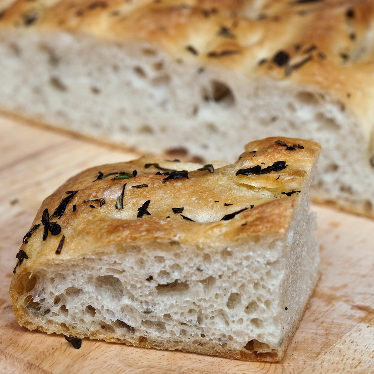 A slice of homemade herbed focaccia bread.