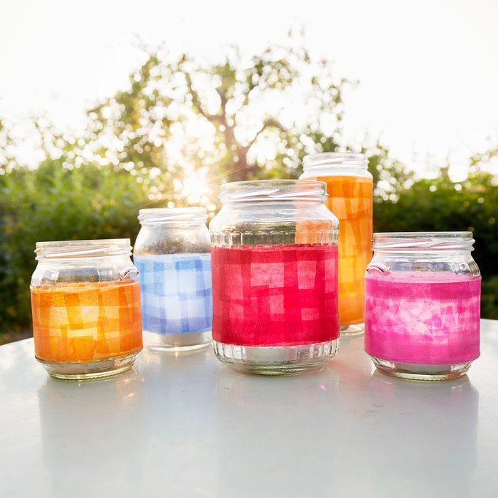 Still Life Of Handmade Lanterns On Table In Garden At Sunset