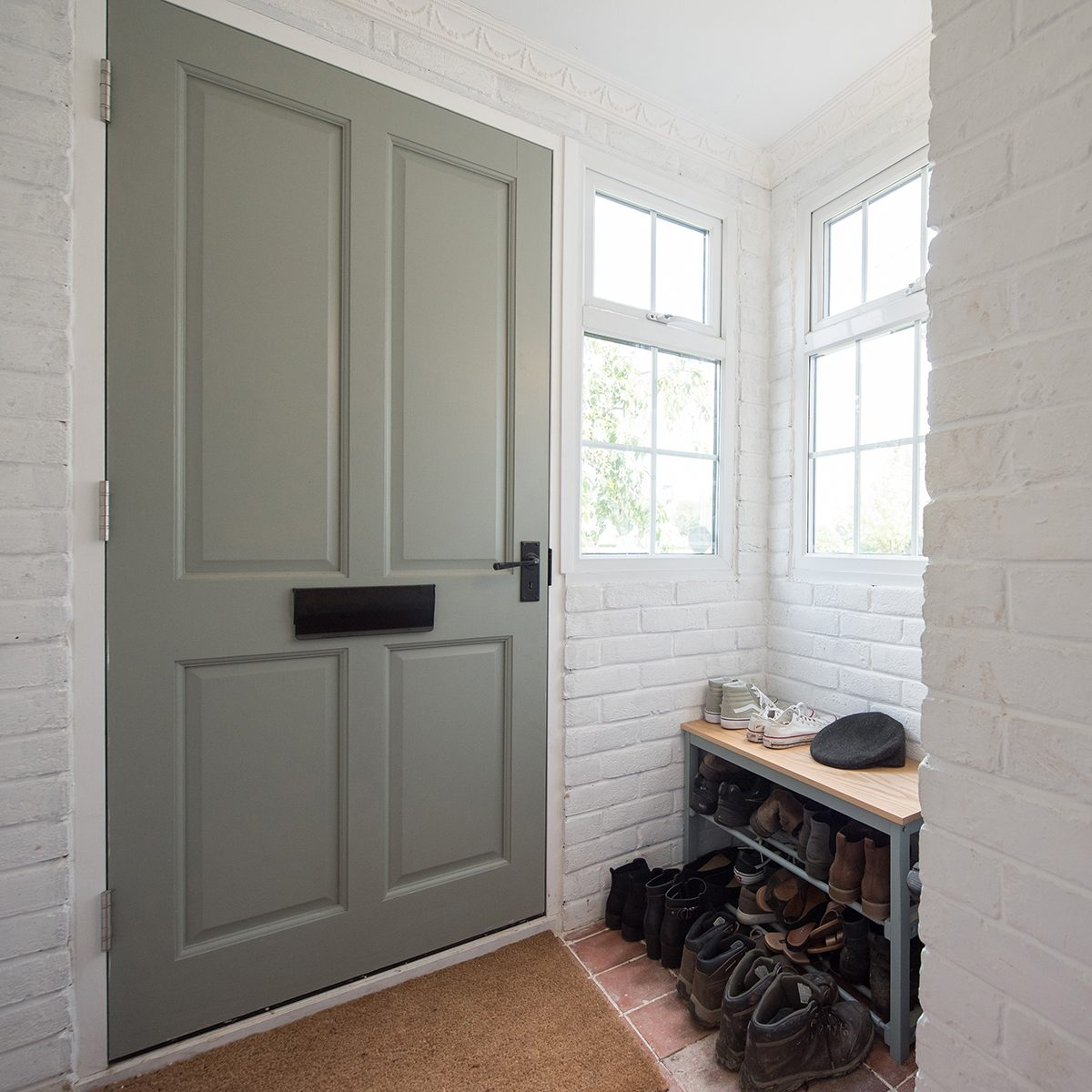 A general interior view of a entrance hall porch with sage green front door and shoe rack storage within a home