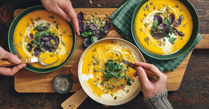 Men eating Vegan Creamy Roasted Pumpkin Soup on wooden background