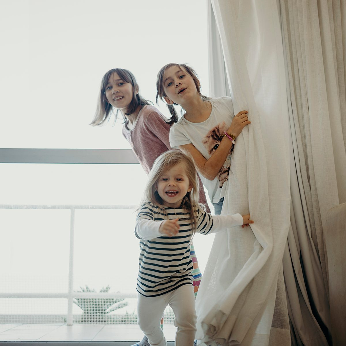 Three Young Girls Peer From Behind Curtain