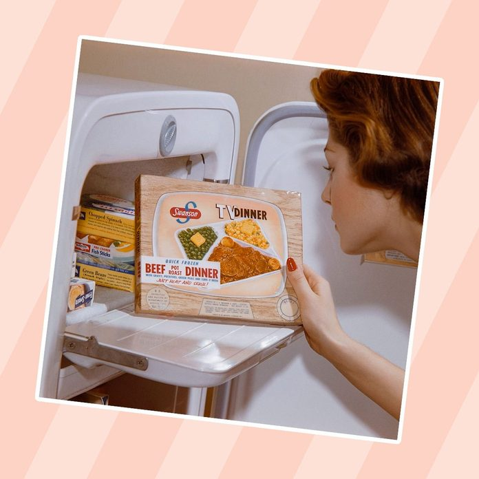 A woman examines a TV dinner box she has taken from the freezer