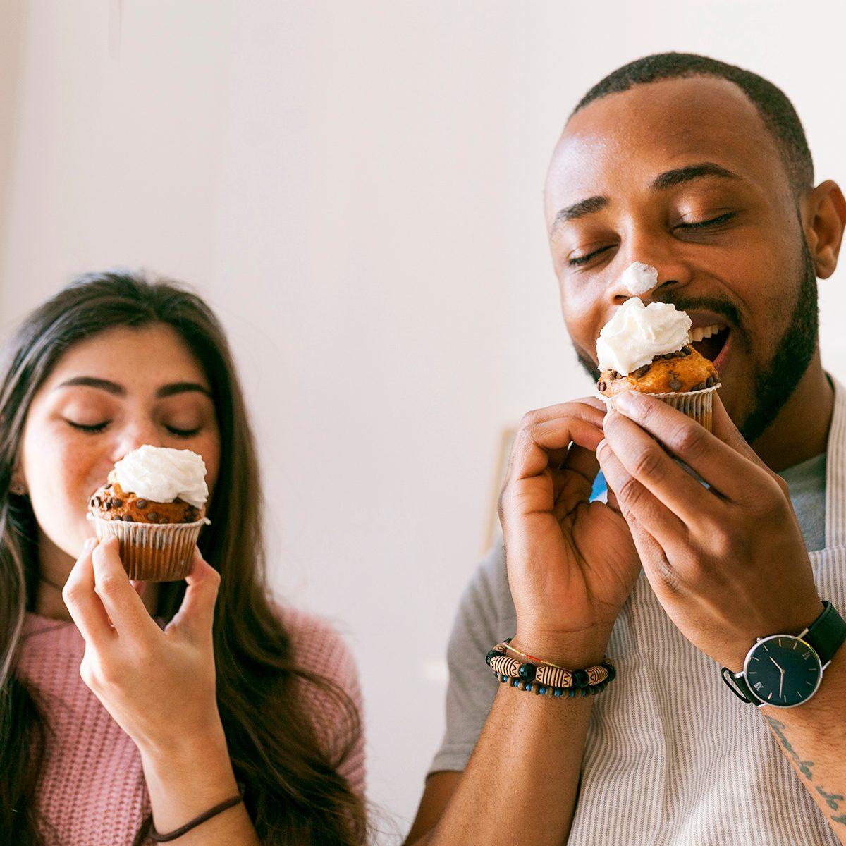 Young Couple Having Fun, Eating Fresh Cupcakes
