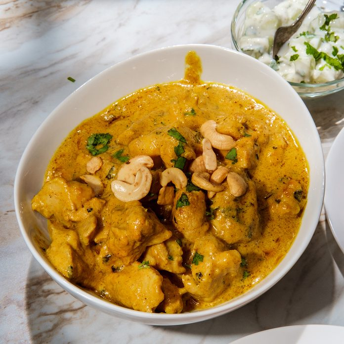 traditional jamaican foods Indian korma curry dinner with raita on marble kitchen table