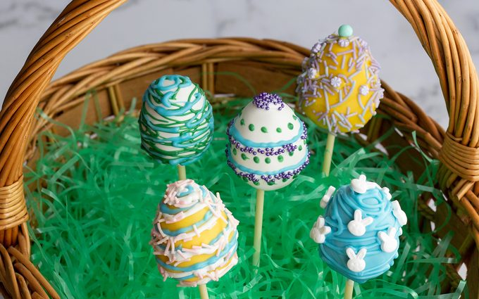 easter cake pops Cake pops in a basket with Easter grass.