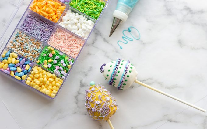 easter cake pops Box with sprinkles next to cake pops.