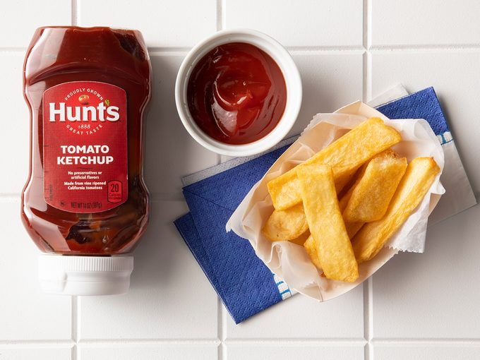 Overhead Shot Of Hunt's Ketchup In Bottle With Fries.
