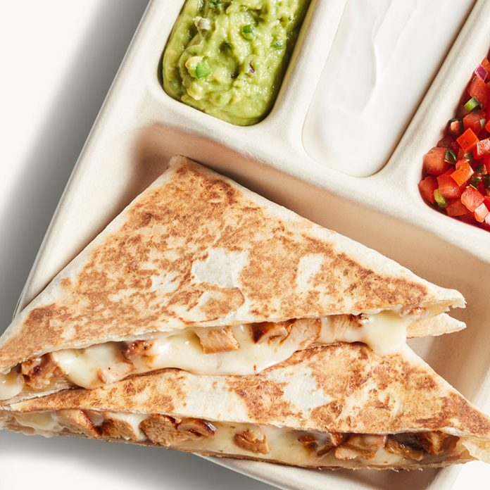 Chipotle's Hand-Crafted Quesadilla is folded and pressed using a new custom oven in Chipotle's Digital Kitchen, which melts the cheese perfectly and enables restaurants to make Quesadillas more quickly and conveniently. The menu item is cut into triangular pieces and served in 100% compostable packaging that allows guests to pick three salsas or sides, including fresh tomato salsa, sour cream, or hand-mashed guac for a little extra.
