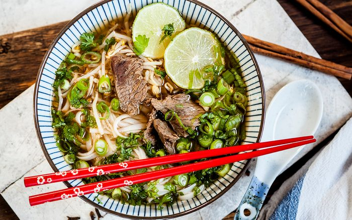 Bowl Of Vietnamese Pho With Rice Noodles, Mung Beans, Cilantro, Spring Onions And Limes